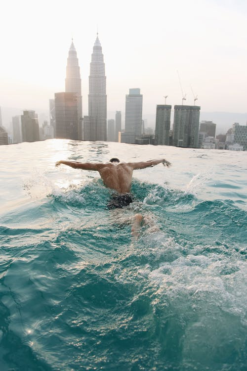Man Swimming in an Infinity Pool