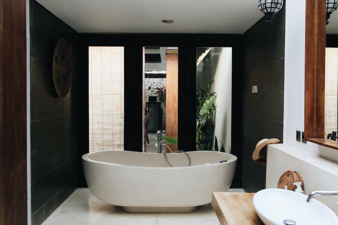 White Bathtub Near Brown Wooden Table