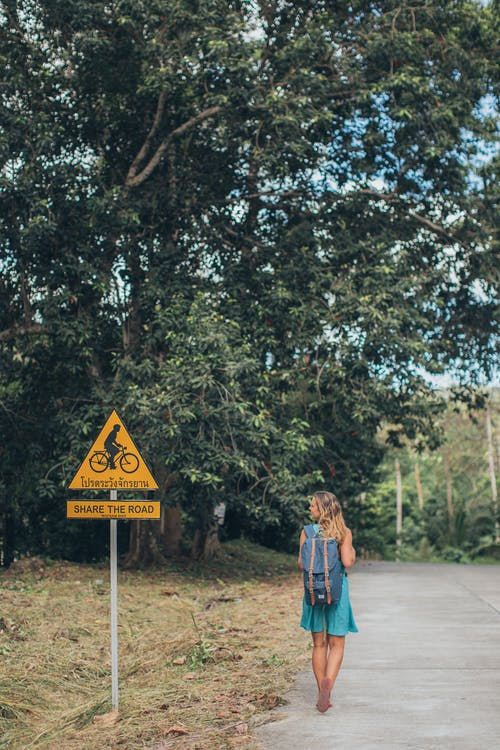 Back view of anonymous young female traveler in dress and backpack walking on path among green trees and bicycle road sign