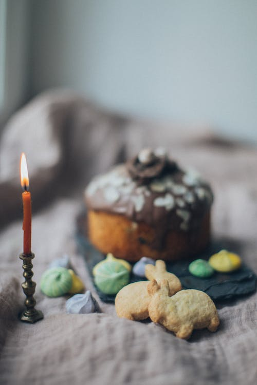 Various Easter cookies and cake composed with burning candle