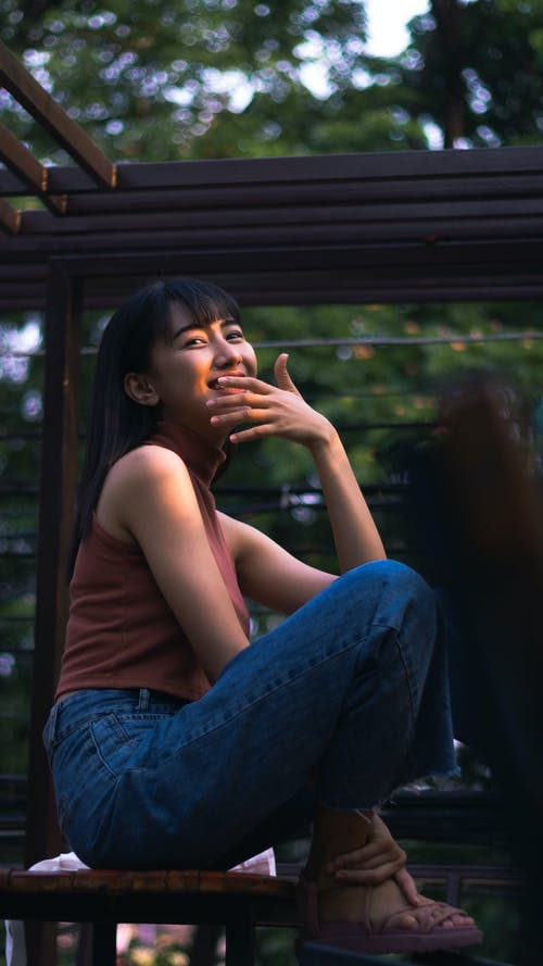 Cheerful young Asian lady having fun on terrace of cafeteria