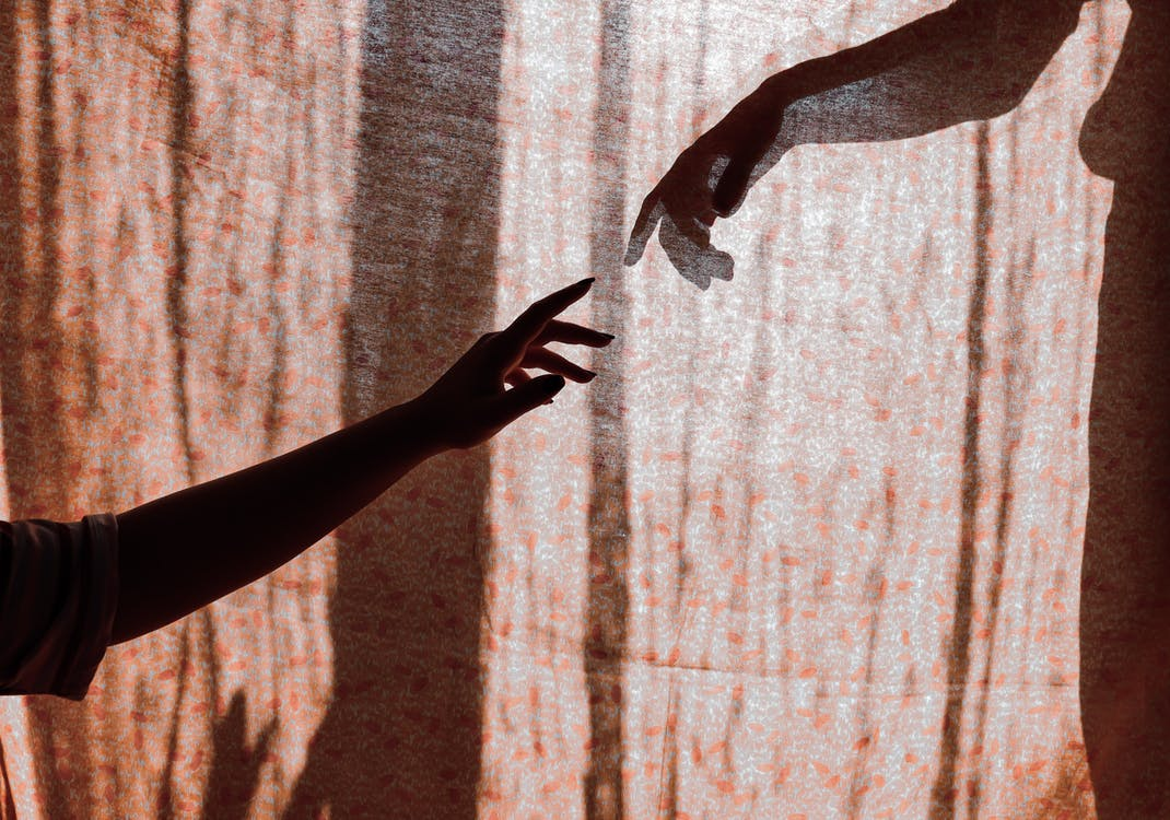 Crop unrecognizable man and woman hands reaching out to each other through translucent curtain on sunny day