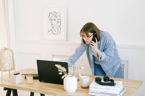 Woman Talking on the Phone and Looking at a Laptop
