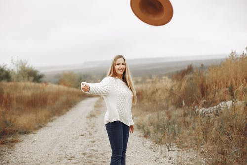 Positive young female with long blond hair in casual clothes throwing hat and smiling while standing on empty rural roadway among dry grass