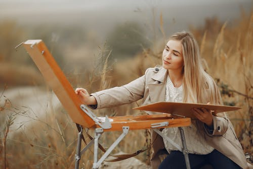 Young focused lady painting picture on nature