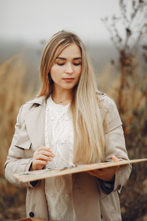 Attentive young woman with palette in field