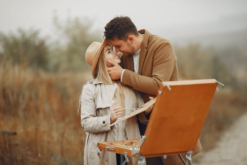 Young happy woman in hat with palette and man in trendy coat smiling and hugging against portable easel in park