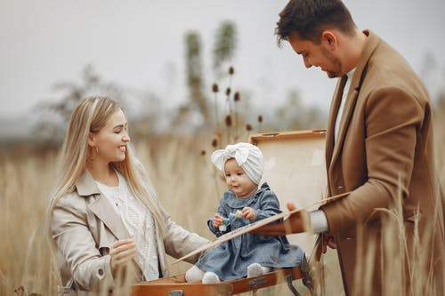 Adorable kid sitting on portable easel in field and playing with happy mother and father