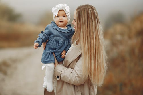 Happy mother standing in park and hugging cute baby