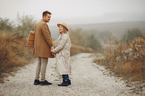 Stylish positive young couple enjoying autumn day in countryside