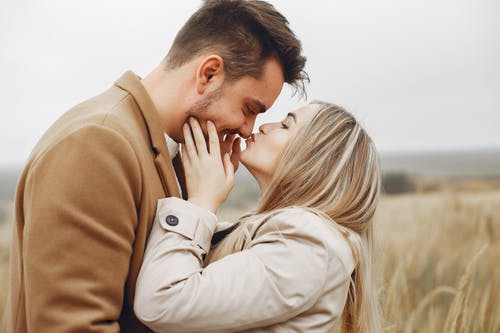 Happy couple embracing in field in autumn day