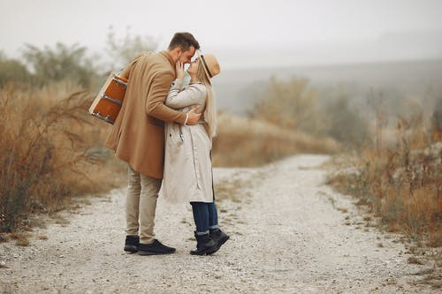 Full body of young romantic couple in stylish coats embracing each other while having date in autumn park