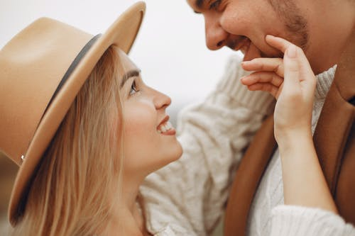 Side view of happy smiling young woman in stylish hat touching face of boyfriend and looking at each other