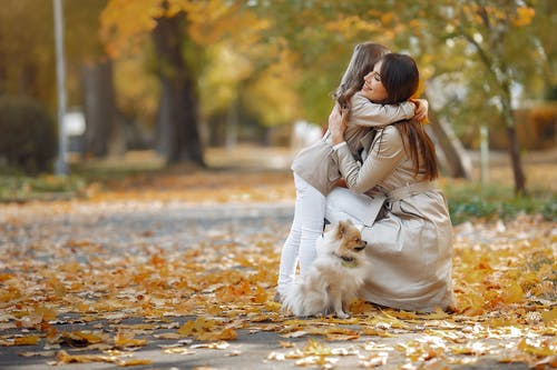 Happy woman hugging little girl in park in autumn day