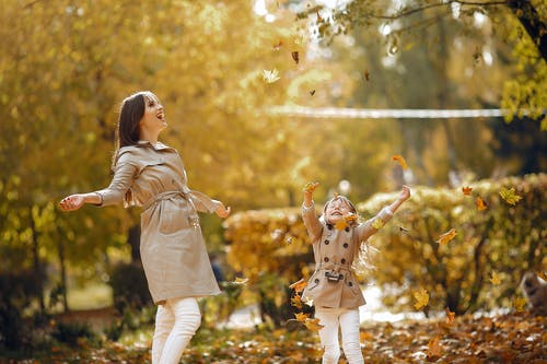 Laughing happy stylish mother and little daughter throwing yellow maple leaves in air while having fun and spending time together in autumn park