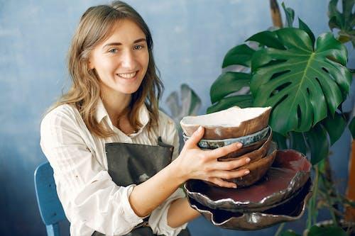 Cheerful female artisan with handmade ceramic dishware