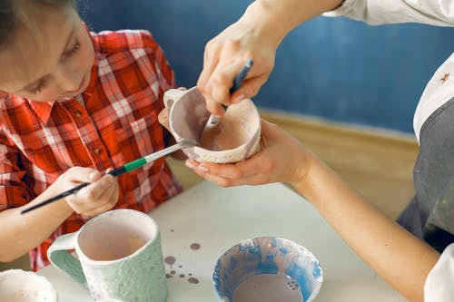 Crop artisan and little girl painting earthware in workshop