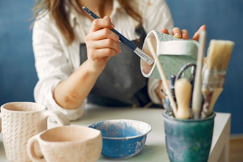 Crop anonymous craftswoman in apron painting handmade ceramic products while working in contemporary creative pottery