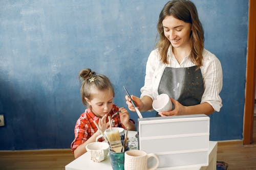 Happy content female ceramist with cute little daughter painting handmade ceramic cups while working in creative workshop together against dark blue wall