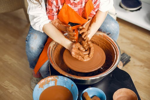 Crop ceramist with little girl working on pottery wheel