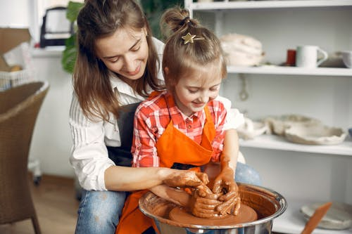 Female potter teaching daughter molding on pottery wheel