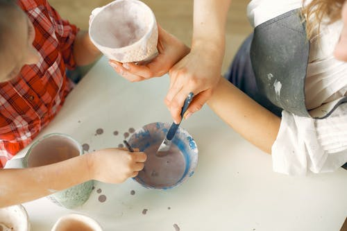 Crop artist with daughter painting earthenware in workshop