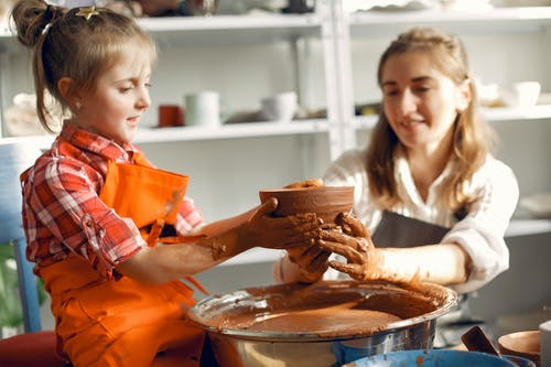 Happy little girl making ceramic bowl with mother in pottery