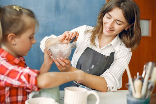 Mother and daughter painting earthenware in pottery