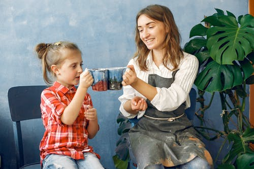 Young smiling female in casual clothes and dirty apron cheering handmade ceramic cups with cute little daughter while sitting together in creative workshop against blue wall