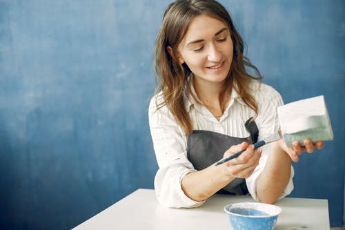 Cheerful craftswoman painting ceramic cup with paintbrush