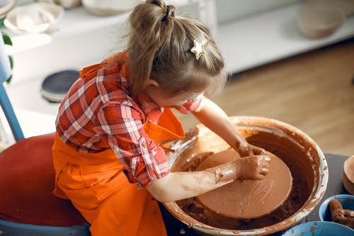 From above  anonymous little girl in red check shirt and apron working with clay on pottery wheel while spending time in workshop
