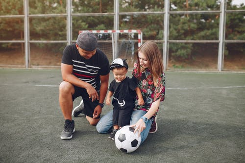 Happy family on football field with ball