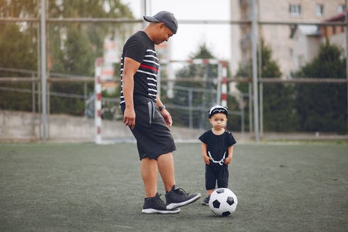 Full body content ethnic father in black casual clothes with cute toddler son kicking football ball while spending time together on sports ground against football gates
