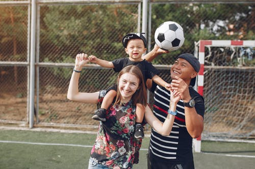 Positive smiling diverse parents giving piggyback ride to adorable toddler son while spending weekend together with football ball on sports ground on sunny day