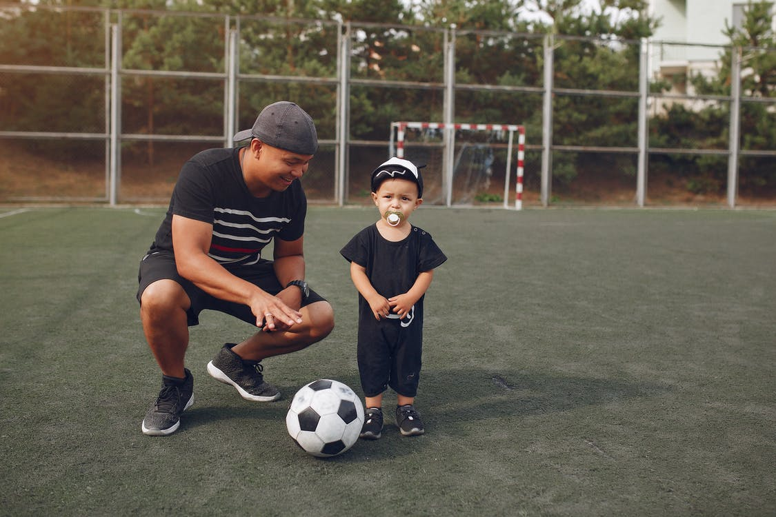 Content father teaching son to play football
