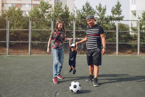 Cheerful family with son and football ball on soccer field