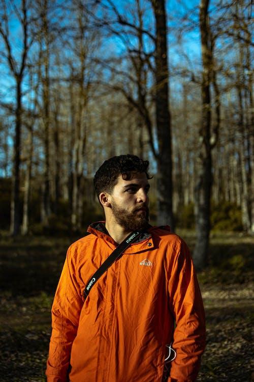 Man in Orange Jacket Standing in Forest