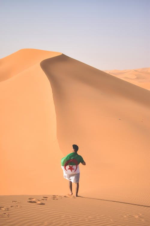 Man in Green Jacket and Black Pants Standing on Brown Sand