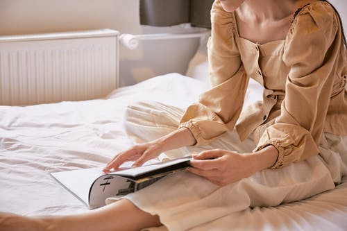 Crop anonymous female in romantic outfit relaxing on bed and reading interesting magazine during weekend at home