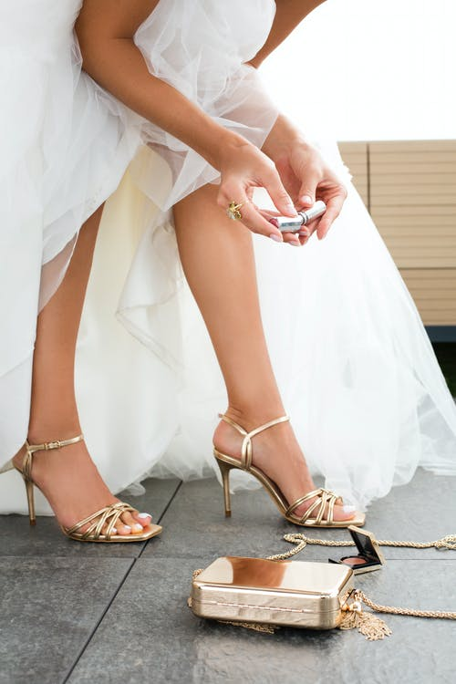 Crop unrecognizable bride in white dress and high heeled shoes holding lipstick in hands while preparing for wedding ceremony