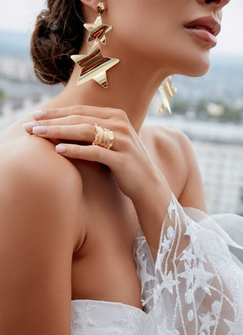 Side view of crop young gorgeous bride in elegant white dress and luxury yellow gold jewelry touching shoulder gently during wedding ceremony
