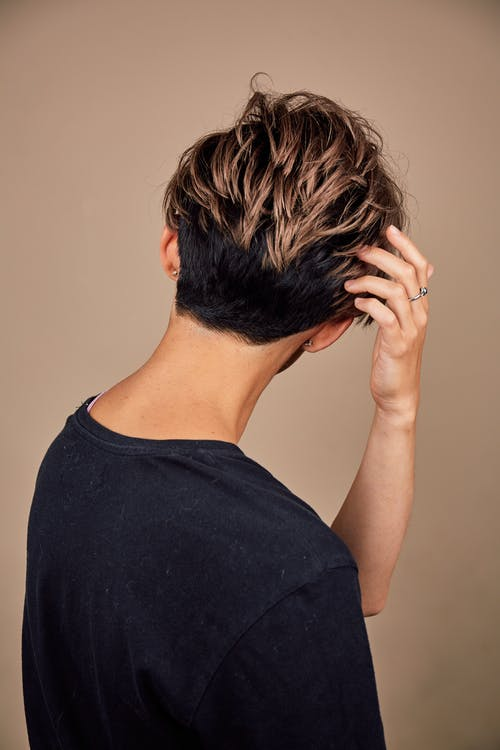 Anonymous young person touching hair and looking away