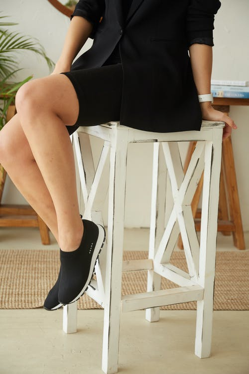 Woman in Black Pants and Black and White Nike Sneakers Sitting on White Wooden Chair