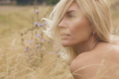Woman in Blonde Hair Standing on Brown Grass Field