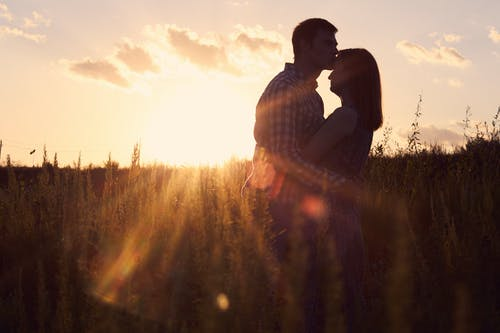 Man and Woman Standing on Grass Field during Sunset