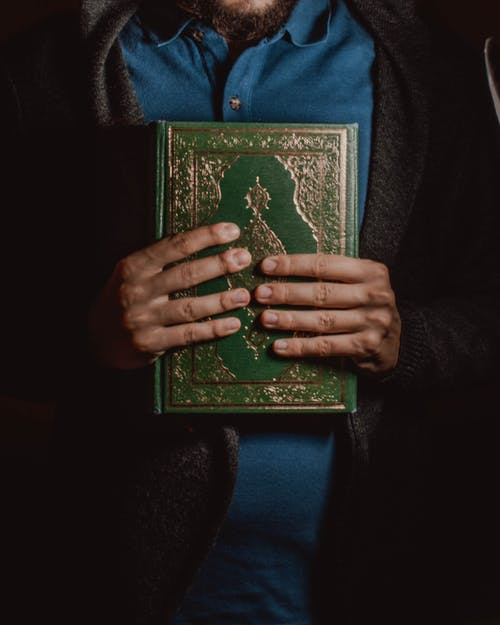 Muslim man with religious book in hands