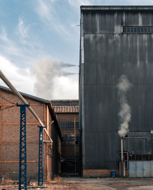Buildings and storage on territory of industrial factory with smoke emitting from pipes against blue sky