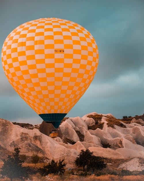 Air balloon flying over rocky formations in countryside