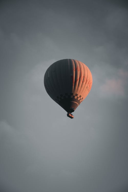 From below of big air balloon flying in gray cloudy sky during sunset