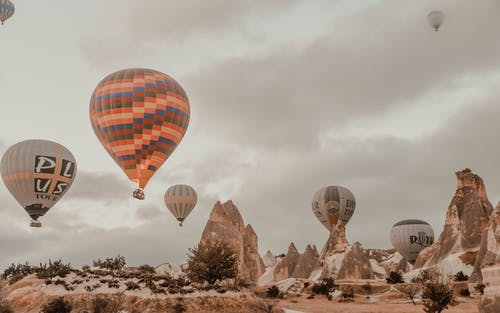 Low angle of multicolored air balloons flying over amazing rocky cliffs in desert valley of Cappadocia against cloudy sky